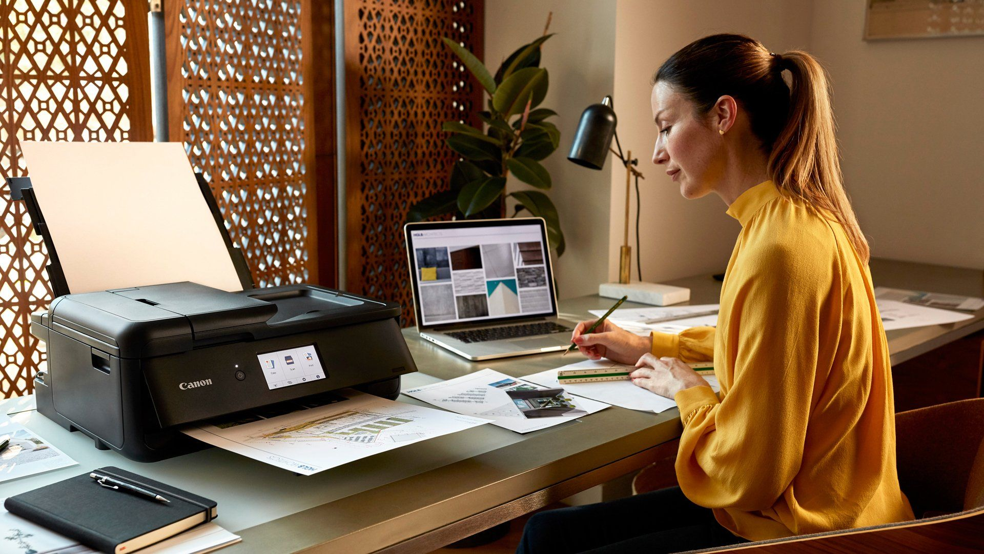 A female business owner prints with PIXMA TS9550 while drawing and using a ruler at her desk.